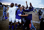 SOWETO, SOUTH AFRICA DECEMBER 27: Soccer players celebrate after a win in an annual tournament on December 27, 2004 in the Meadowlands section of Soweto, Johannesburg, South Africa. The yearly event draws teams from surrounding townships, and people love the game of soccer in the township. Soweto is South Africa&rsquo;s largest township and it was founded about one hundred years to make housing available for black people south west of downtown Johannesburg. The estimated population is between 2-3 million. Many key events during the Apartheid struggle unfolded here, and the most known is the student uprisings in June 1976, where thousands of students took to the streets to protest after being forced to study the Afrikaans language at school. Soweto today is a mix of old housing and newly constructed townhouses. A new hungry black middle-class is growing steadily. Most residents work in Johannesburg but the last years many shopping malls has been built, and people are starting to spend their money in Soweto. <br /> (Photo by Per-Anders Pettersson)