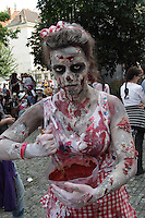 "woman from prague zombie walk 2014, looking at the camera, stirring in a bowl of ""blood"", having ""Scars"" on arms and in the head, wearing a white and red apron."