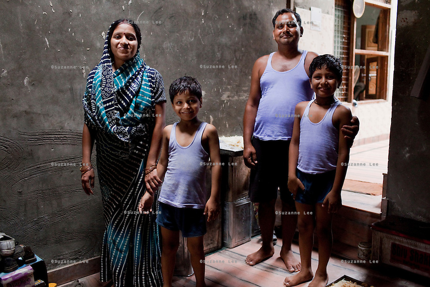 Seema Gupta (aged 34, far left) and Ramesh Chandra Gupta (38) pose for a family portrait in their shophouse in Ghaziabad, Uttar Pradesh, India. Seema Gupta had a tubectomy done on 9 June 2011 for family planning while her husband, Ramesh Chandra Gupta, wasn't aware of the option and benefits of non-scalpel vasectomy (NSV). They run a roadside sweets shop at the front of their house and chose to have a family planning surgery done as they did not want to compromise the quality of life for their two children. While Ramesh wanted only 1 child, both his mother and Seema pushed for a 2nd child. Photo by Suzanne Lee / Panos London