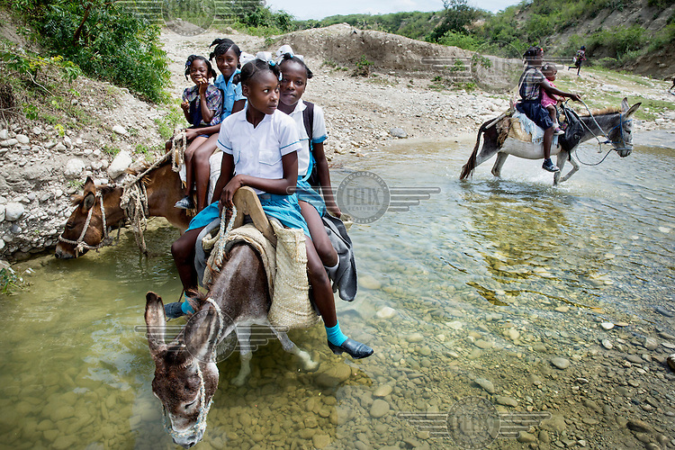 Schoolgirls ride a donkey across the river Moustique. This river is the main irrigation water source in this parched region. In 2011, according to WHO and UNICEF, only 48 percent of the rural population had access to drinking water and only 29 percent had sanitation facilities.