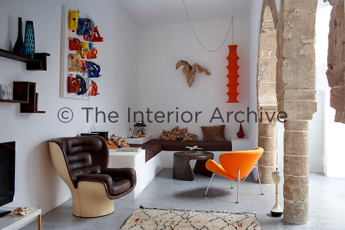 Retro designer chairs furnish this living room which has an additional moulded corner banquette and original stone pillars