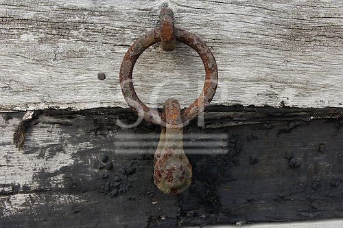 Orford, Suffolk; iron ring and shackle on the side of a fisherman's hut with weatherboarding of different ages and conditions.