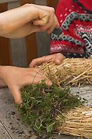 Kinder basteln einen Lichterkranz für die Adventszeit, Adventskranz, Kind bindet Moos mit Draht auf einen Unterkranz aus Stroh