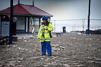 Monday 06 January 2014<br /> Pictured: Coastguards help to  clear the promenade asThe Sea batters Aberystwyth Seafront<br /> Re: Storm force winds and high tides hit the UK