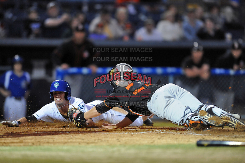 Delmarva Shorebirds catcher Chance Sisco #23 tags out a hard sliding David Dahl #21 during a game against the Asheville Tourists at McCormick Field on April 4, 2014 in Asheville, North Carolina. The Shorebirds defeated the Tourists 7-2. (Tony Farlow/Four Seam Images)