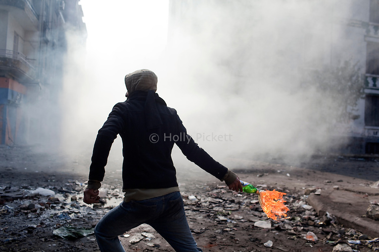 A protester throws a molotov cocktail at police on Mohamed Mahmoud Street near Tahrir Square in Cairo, Egypt, Tuesday, November 22, 2011. Clashes between Central Security Forces and demonstrators against military rule continued into a fourth day.