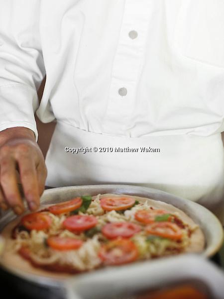 A chef makes a pizza at Six Senses Hideaway Yao Noi's show kitchen. Thailand.