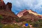 A tent at cottonwood campground below colorful canyon walls in sunlight. On the bright angel trail in grand canyon