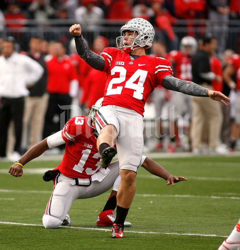 Ohio State's Drew Basil (24) watches an extra point against Illinois in the 1st half of their NCAA football game at Ohio Stadium, November 3, 2012. The holder is Kenny Guiton. (For the Dispatch by Mike Munden )