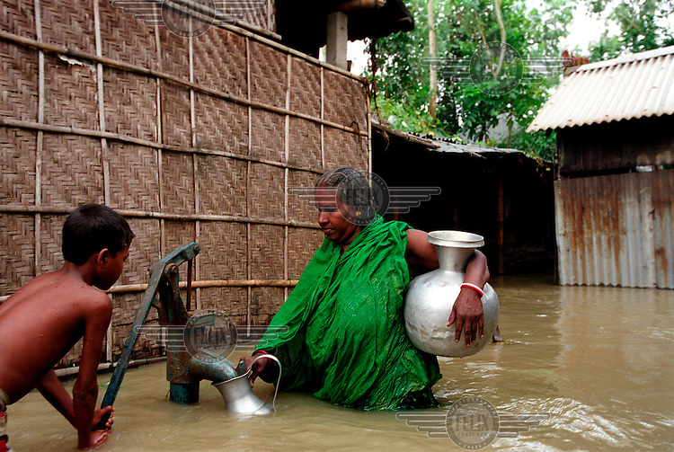 People collecting fresh water during floods. Monsoon rains caused flooding in 40 of Bangladesh's 64 districts, displacing up to 30 million people and killing several hundred.