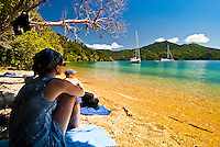 Woman enjoying summer on Governors Beach near Picton - Marlborough Sounds , New Zealand