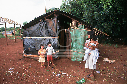 Rio Grande do Sul, Brazil. Guarani Indian mother holding her baby with two toddler children in front of their makeshift shack.