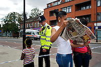 A woman reads a copy of The Sun newspaper as a child talks to a policeman at a cordoned area where rioting took place two nights earlier in Tottenham, London borough of Haringey. London saw the beginnings of riots on Saturday evening, after a peaceful protest in response to the shooting by police of Mark Duggan during an attempted arrest, escalated into violence. By the third night of violence, rioting had spread to many areas of the capital and to other cities around the country.