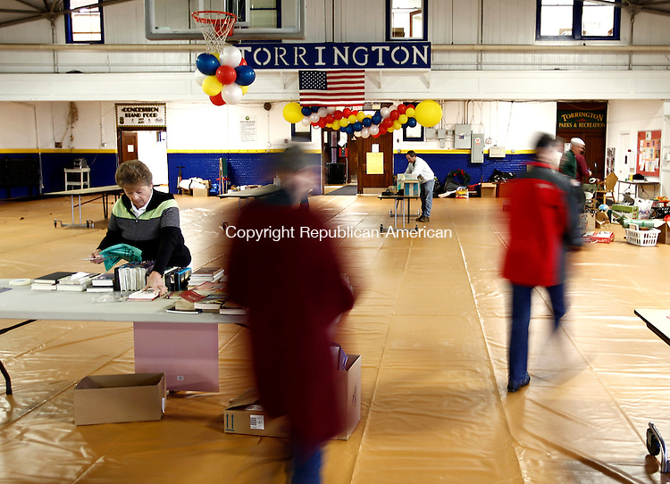 Torrington, CT- 12 April 2013-041213CM03-  Carolyn Mosher, left, of Torrington sets up the movies and book table at the Torrington Armory Friday afternoon.  City officials and volunteers accepted items and began setting up for the Community Tag Sale, a fundraiser to benefit the city's Fireworks Fund.  The tag sale will run Saturday from 9 a.m. through 4 p.m.   Christopher Massa Republican-American