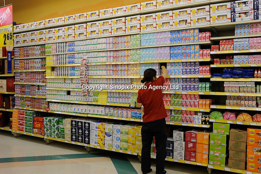Staff putting UHT milk on shelf in Shenyang, China. the British retailer is undergoing an aggressive expansion and attempting to capture the growing middle class market in food and other domestic merchandise in China..