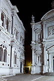 ITALY, Venice. A partial night view of the facades of the Scuola Grande di San Rocco, art museum, on the left and the Chiesa San Rocco on the right.