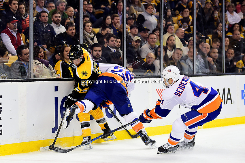 Tuesday, December 20, 2016: New York Islanders defenseman Dennis Seidenberg (4) reaches in to get the puck freed by a check on Boston Bruins center Ryan Spooner (51) by defenseman Johnny Boychuk (55) during the National Hockey League game between the New York Islanders and the Boston Bruins held at TD Garden, in Boston, Mass. The Islanders defeat the Bruins 4-2. Eric Canha/CSM