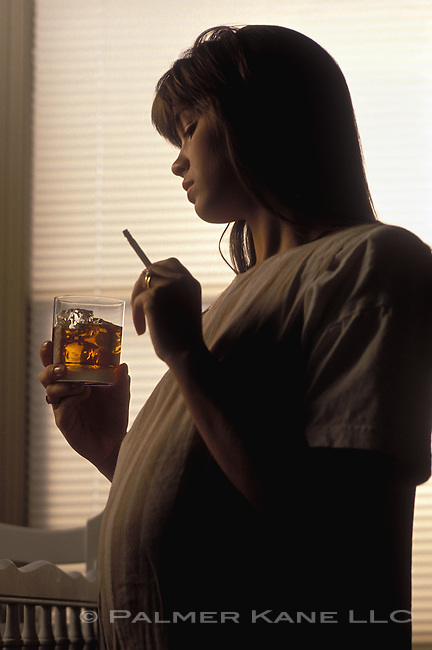 Pregant Woman in Dim lighting holding a drink and smoking a cigarette