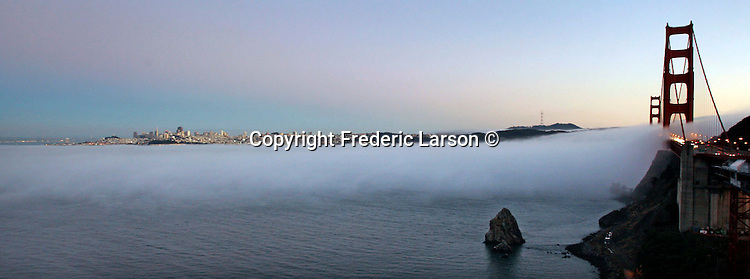 San Francisco fog slowly creeps under the Golden Gate Bridge as seen from the north side vista point in Sausalito, California.