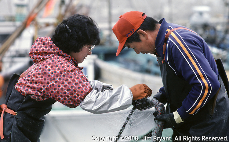 A woman helps her husband untangle their nets for the next day of fishing off the Strait of Tsugaru in the fishing port town of Omma, on the Northern most tip of Honshu, Japan. (Jim Bryant Photo)