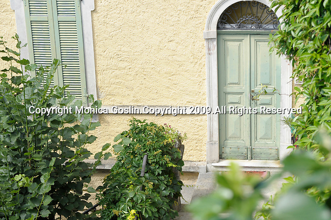 A pale yellow house with pale green shuddered windows and a pale green door in Oria, a town in the mountains on Lake Lugano, Italy.