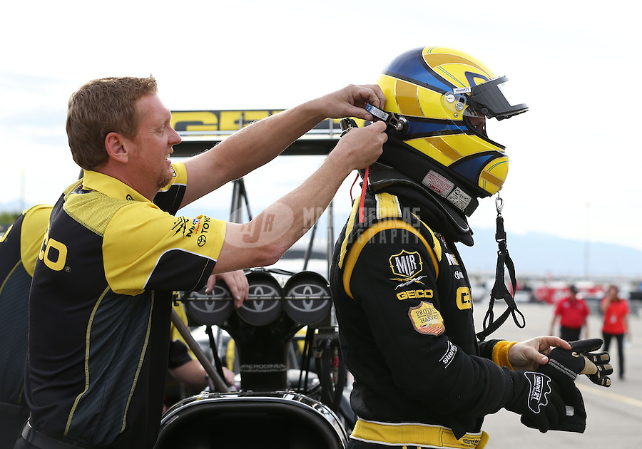 Apr. 5, 2013; Las Vegas, NV, USA: NHRA crew member helps connect the hans device on top fuel dragster driver Morgan Lucas during qualifying for the Summitracing.com Nationals at the Strip at Las Vegas Motor Speedway. Mandatory Credit: Mark J. Rebilas-