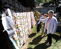 NWA Democrat-Gazette/ANDY SHUPE<br /> Diane Pennington (right) of Lowell speaks with Lois Arnold of Springdale Saturday, Sept. 12, 2015, while describing a Wedding Ring-pattern quilt that her 102-year-old grandmother, Vola Watson-Edgmon of Lowell, began and Pennington finished by hand during the 38th annual Ozark Quilt Fair at the Shiloh Museum of Ozark History in Springdale. The fair included historic and newly made quilts as well as opportunities to visit with area quilters.