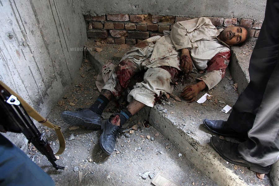 KABUL, Afghanistan: Afghan policemen and security officials stand over a militant body after a gun battle in Kabul, Afghanistan, Monday, April 16, 2012. A brazen, 18-hour Taliban attack on the Afghan capital ended early Monday when insurgents who had holed up overnight in two buildings were overcome by heavy gunfire from Afghan-led forces and pre-dawn air assaults from U.S.-led coalition helicopters.