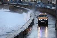 Pictured: Huge waves crashing against the promenade wall while a Coastguard 4x4 vehicle is patrolling the area in Porthcawl, south Wales. Friday 03 January 2014<br /> Re: Flood warnings have been issued  by the Environment Agency due to strong winds and high tides for part of the UK.