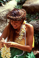 Young girl wearing a haku lei makes plumeria leis at Waimea Falls on Oahu.