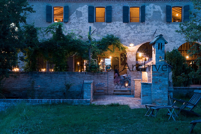 The converted water mill seen from the garden looks beautiful lit up at night