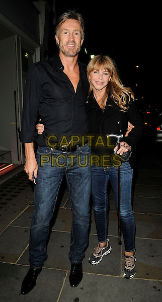 LEE CHAPMAN & LESLIE ASH.The Juju party, Juju bar & restaurant, King's Rd., London, England..September 3rd, 2009.full length black shirt jacket cane walking stick sneakers trainers married husband wife stubble beard facial hair .CAP/CAN.©Can Nguyen/Capital Pictures.