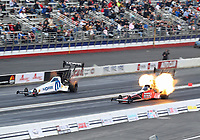Feb 9, 2020; Pomona, CA, USA; NHRA top fuel driver Leah Pruett (left) races alongside Shawn Reed as he explodes an engine on fire during the Winternationals at Auto Club Raceway at Pomona. Mandatory Credit: Mark J. Rebilas-USA TODAY Sports