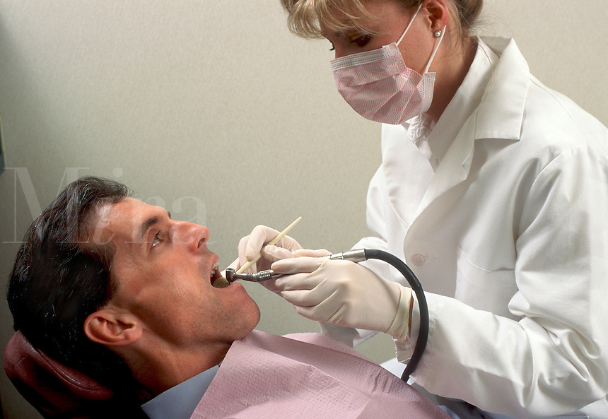 A dentist drills a man's tooth in to prepare it for a filling.