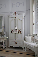 A large wooden wardrobe and hand-painted settle in the bedroom