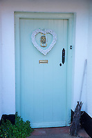 Cottage front door with tongue and groove panels painted pastel mint green and old-fashioned broomstick in Dunster, Somerset, UK