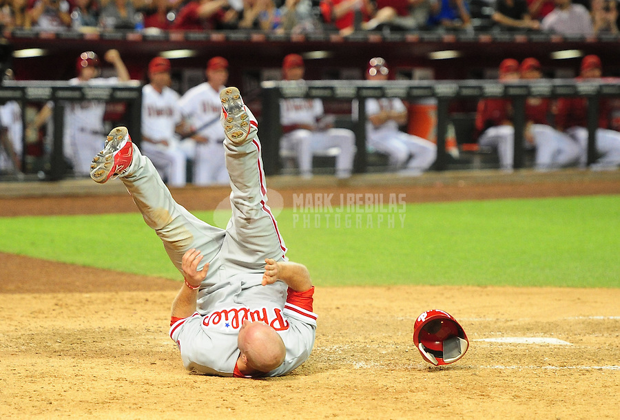 Apr. 23, 2012; Phoenix, AZ, USA; Philadelphia Phillies base runner Pete Orr flips over after being tagged out at the plate in the eighth inning against the Arizona Diamondbacks at Chase Field. Mandatory Credit: Mark J. Rebilas-
