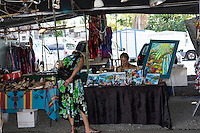 A local Hilo artist talks with a customer at the famous Hilo Farmers Market, Big Island of Hawai'i.