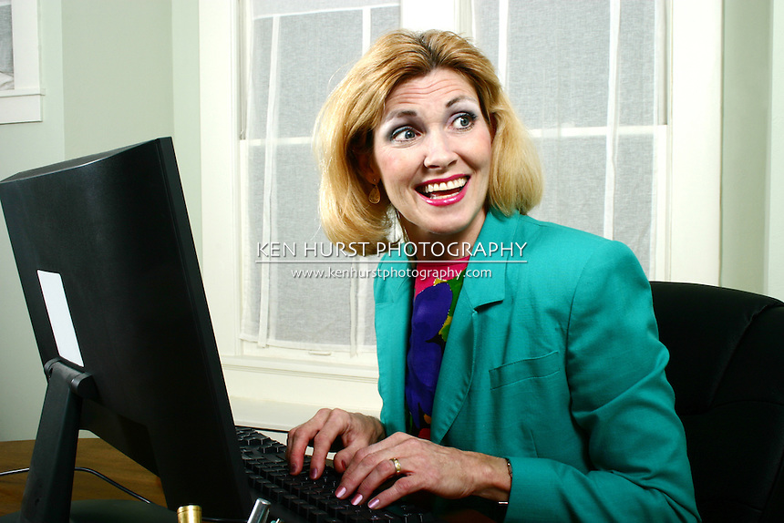 Beautiful middle aged executive business woman laughing with off-stage co-workers while typing on her computer in the office.