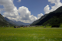 Alpine meadows cow shelters and town of Imst overlooked by mountains and forests. Imst district, Austria.