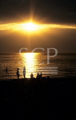 Melbourne, Australia. People silhouetted on St. Kilda beach against golden light reflected off water.
