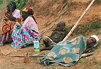 Rwandans rest after being seen by doctors or while waiting for loved ones receiving treatment at the AmeriCares clinic in Buranga, Rwanda, Oct., 1994. The New Canaan, Conn., organization operated a clinic  from Aug., to Dec., 1994 halfway between the capitol, Kigali and the refugee camps in Goma, Zaire (now Congo). The treated refugees on their way home as well as people living in the area suffering from ailments resulting from unclean living conditions as well as conflicts with neighbors and occasional discovery of unused ordinance littering the countryside.  The living conditions resulted from the destruction of the country's infrastructures in the genocide and civil war in 1994.