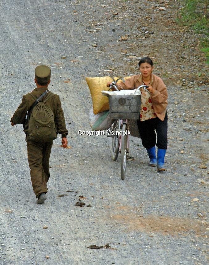 A farmer walks pass a soldier in PyongYang, North Korea.