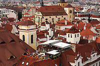 Editorial use only.<br /> <br /> A view over the red roofs in prague, with towers,church and an outdoor restaurant.