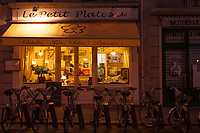 """Bicycles parked outside the """"Le Petit Plateau"""" cafe at nightfall in Paris."""