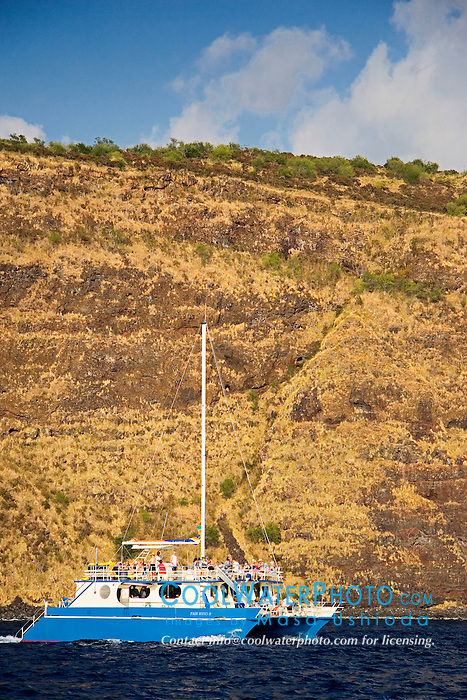 Sheer cliffs of Kealakekua Bay dwarfing 60 foot custom catamaran, Fairwind II, charter boat, Captain Cook, Big Island, Hawaii, Pacific Ocean