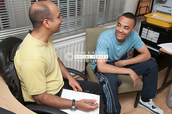 Teenage boy and Social worker in hostel office.