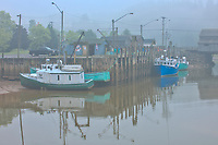 Fishing boats in fog. Coastal fishing village.<br />