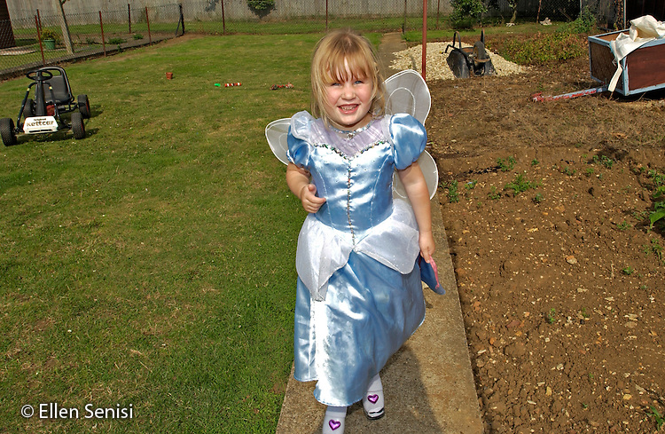 MR / Radley, Abingdon, Oxfordshire, England.Girl (5) in dress-up clothes plays in her backyard..MR: Web4.©Ellen B. Senisi