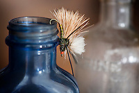 A Stimulator dry fly rests on an old bottle at the Henneberry Homestead on the Beaverhead River near Dillon, Montana.